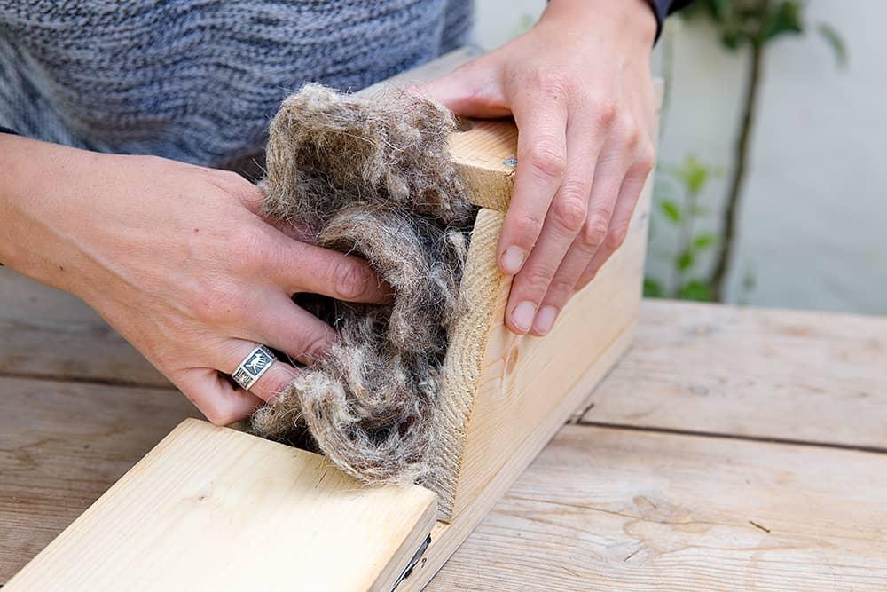 Vul de nestkast met isolerend materiaal, zoals wol