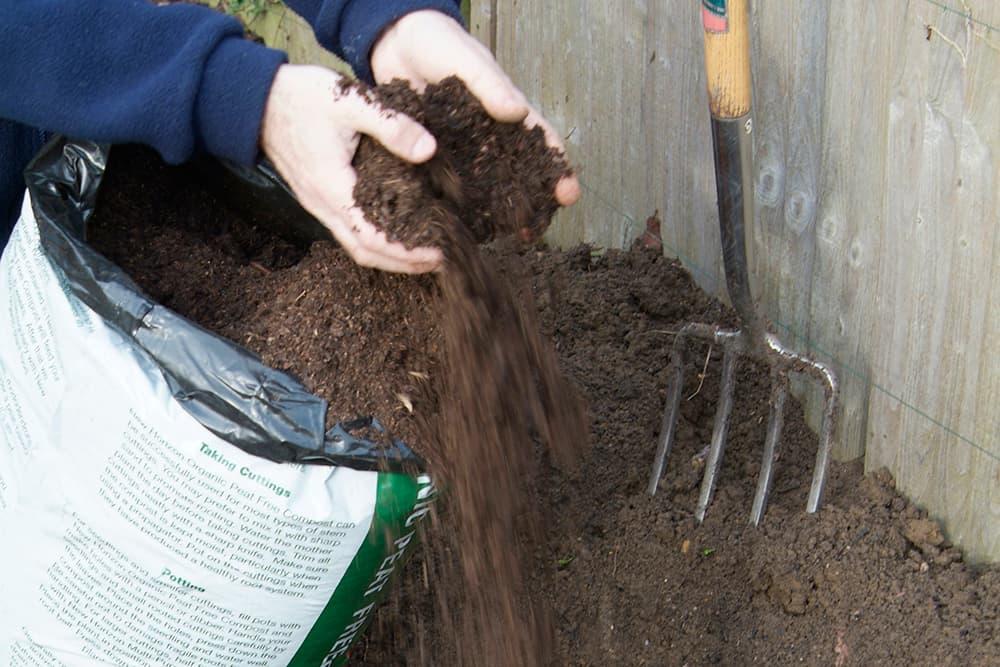 Doe potgrond in het plantgat.