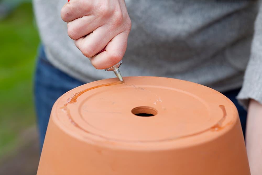 Spuit lijm onder de terracotta pot.