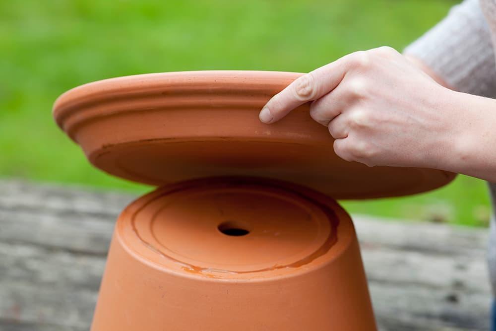 Plak de schotel van je vogelbad vast aan de terracotta pot.